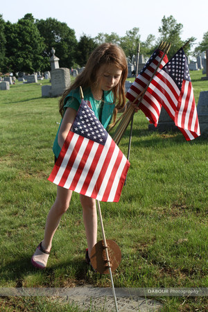 Girl Scout Morrissey Mchenry, 10 from Alpha puts out a US flag on a grave site.