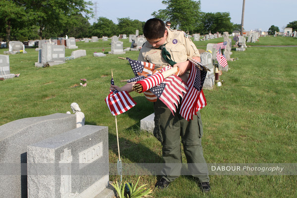 Boy Scout Justin Dimersico, 12 from Pohatcong Township puts out a US flag on a grave site.