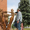 "Joe Dugas helps with the sculpture care of the ""Three Muses"" by the east entrance of the Old Administration Building.  (photo by Bethany Cook)"