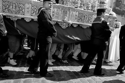 """20 tot 24 dragers die de """"praalwagen"""" een deel van de processie dragen. Toevallig was dit precies een moment waarop het doek iets opgerold was i.v.m. de hitte. De matroos heeft mij in de gaten."""