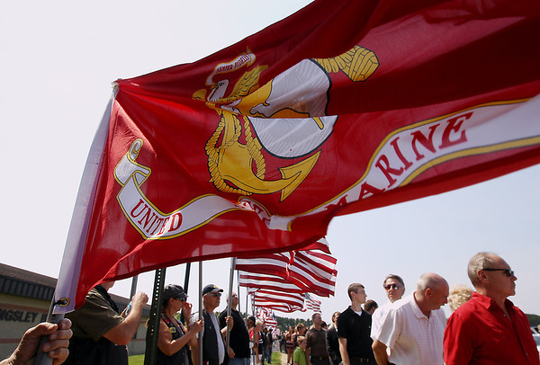 Record-Eagle/Keith King<br /> Flags blow in the wind prior to the start of the funeral for United States Marine Sgt. Justin Hansen Saturday, August 4, 2012 as attendees wait to enter the gymnasium of Kingsley High School.