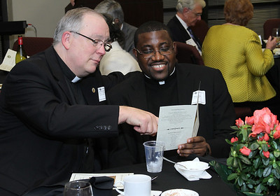 Father Dan Stack, left, the pastor at St. Francis of Assisi Church, Cartersville, and Father Henry Atem, parochial vica at St. Patrick Church, Norcross, look over the program for the evening.