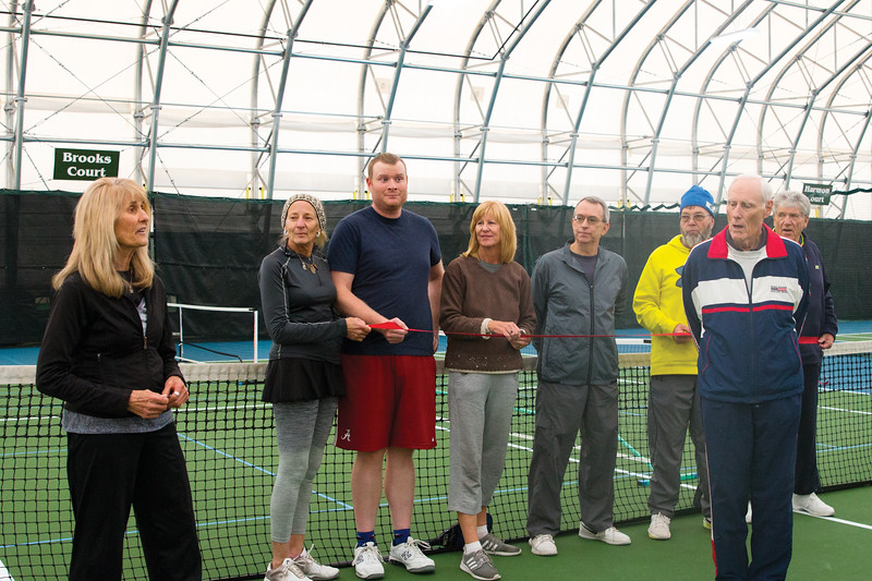Matthew Gaston | The Sheridan Press<br>Lorna Brooks far left and the Sheridan Community Tennis Association Board from left, Terry Henn, Owen Mullinax, Polly Grimshaw, Rick Schmierer, Arlie Johnson, Ken Harmon and Bill Brooks participate in the ribbon cutting for the Sheridan Community Tennis Center's grand opening Saturday, Dec. 1, 2018. Although the Sheridan Community Tennis Center has been in operation for three years, the Board wanted to wait for the grand opening until they could have the two tennis courts resurfaced. Resurfacing was completed two weeks ago.