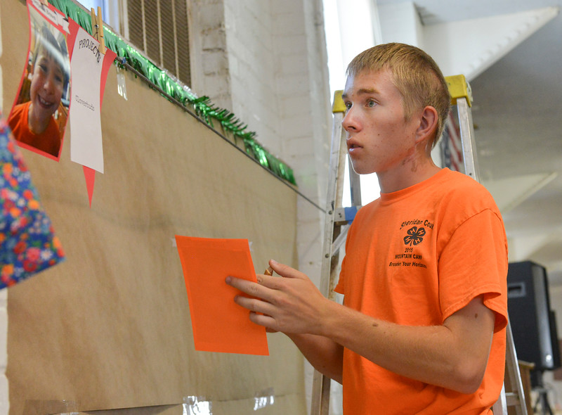 Justin Sheely | The Sheridan Press<br /> Seventeen-year-old Nathan Petzold hangs portraits over his 4-H club booth in preparation for the Sheridan County Fair at the Sheridan County Fairgrounds Tuesday, July 31, 2018.