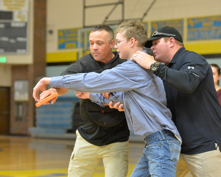 Ryan Patterson | The Sheridan Press<br /> From left: TAC*ONE Consulting founder and president Joe Deedon, Arvada-Clearmont High School sophomore Ethan Packard and TAC*ONE Consulting trainer Brian Pollard simulate responding to an active shooter during school safety training at the Arvada/Clearmont K-12 School Thursday, Nov. 29, 2018. Students, educators, community members and law enforcement participated in training over the course of three days.