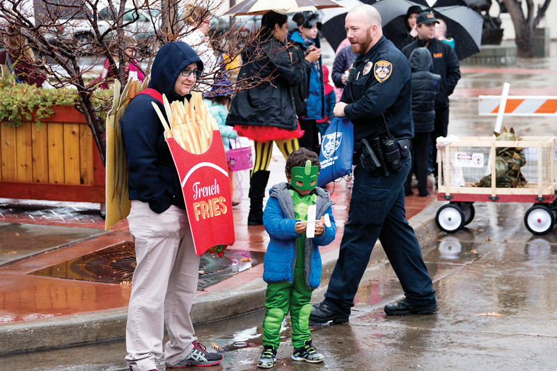 Matthew Gaston | The Sheridan Press<br>Five-year-old Theodore Mutch, center, immediately begins to play with a wooden airplane he recieved from officer Matt Misslier, right, while trick-or-treating with his mother Jenny Mutch, left, at the Halloween Parade Saturday, Oct. 27, 2018.