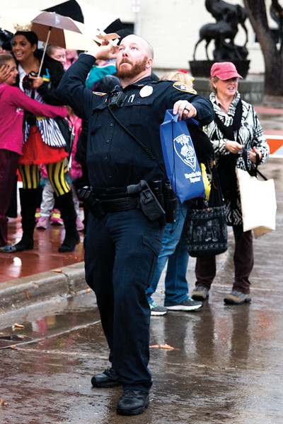 Matthew Gaston | The Sheridan Press<br>Sheridan police officer, Matt Misslier, demostrates the proper form for playing with the wooden planes the police department was handing out with candy during the Halloween Parade Saturday, Oct. 27, 2018.