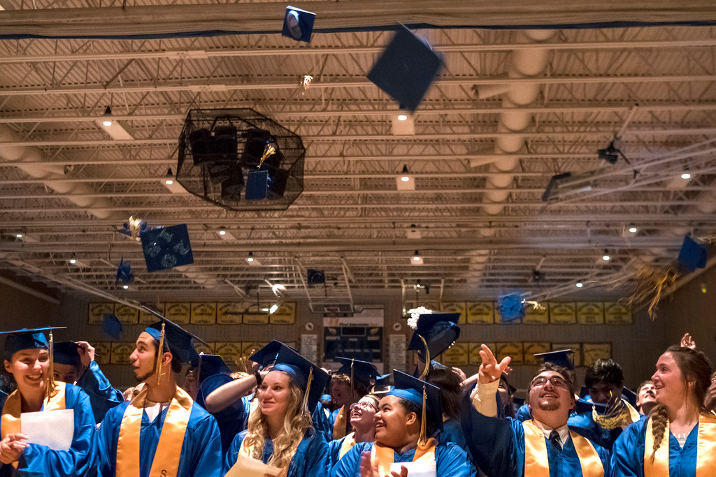 Justin Sheely | The Sheridan Press<br /> Graduates toss their caps during the class of 2018 commencement ceremony at Sheridan High School Sunday, May 27, 2018.