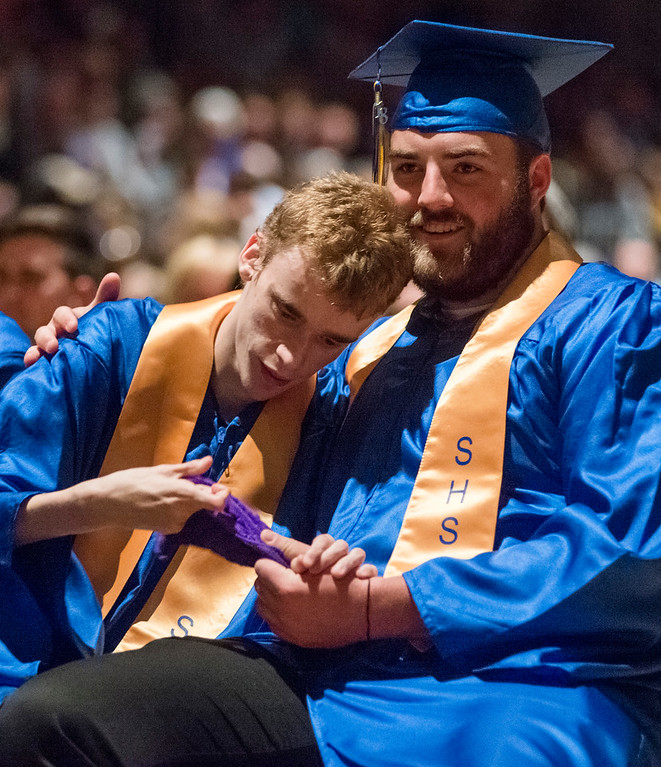 Justin Sheely | The Sheridan Press<br /> Blayne Baker, right, assists Austin Wright during the class of 2018 commencement ceremony at Sheridan High School Sunday, May 27, 2018.