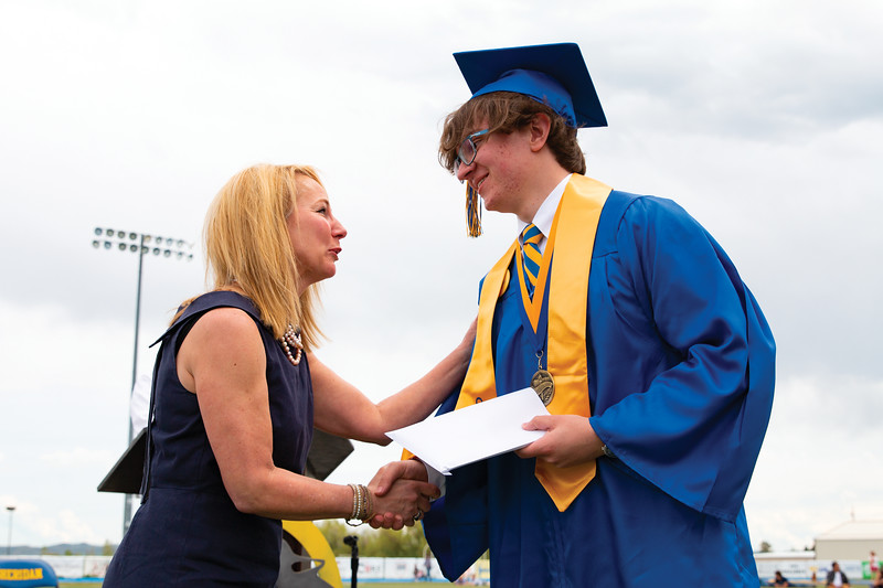 Matthew Gaston | The Sheridan Press<br>School board trustee Arin Waddell congratulates Sheridan High School's valedictorian William Card during commencement Sunday, May 26, 2019.
