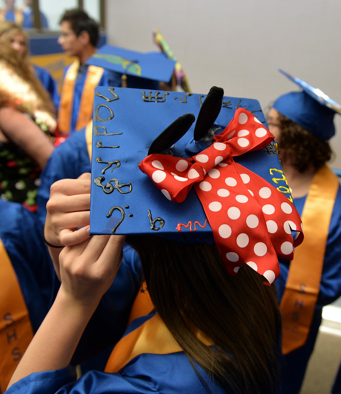 Justin Sheely | The Sheridan Press<br /> A graduate pins her hat down prior to the 2017 graduation ceremony Saturday at Sheridan High School.