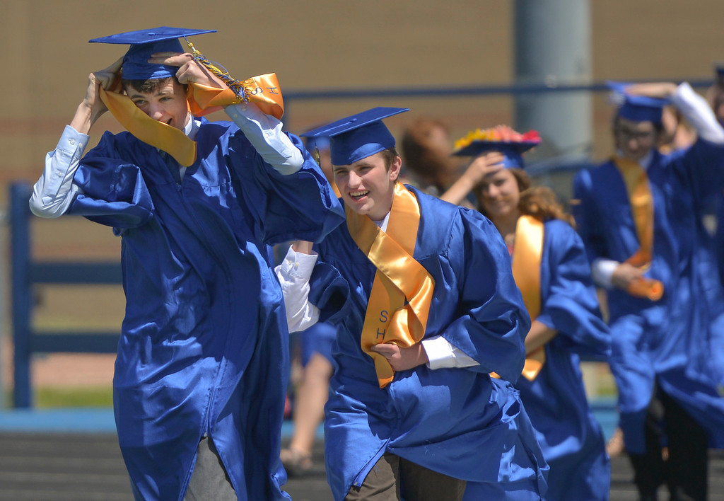 Justin Sheely | The Sheridan Press<br /> Culley Emborg, left, and Matthew Eisenhauer battle the wind as their march across Homer Scott Field during the 2017 graduation ceremony Saturday at Sheridan High School.