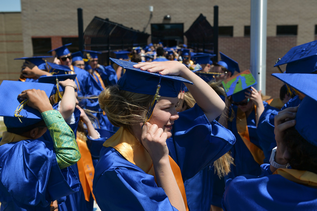 Justin Sheely | The Sheridan Press<br /> Brenna Kysar holds her hat against the wind as graduates line up outside the field during the 2017 graduation ceremony Saturday at Sheridan High School.