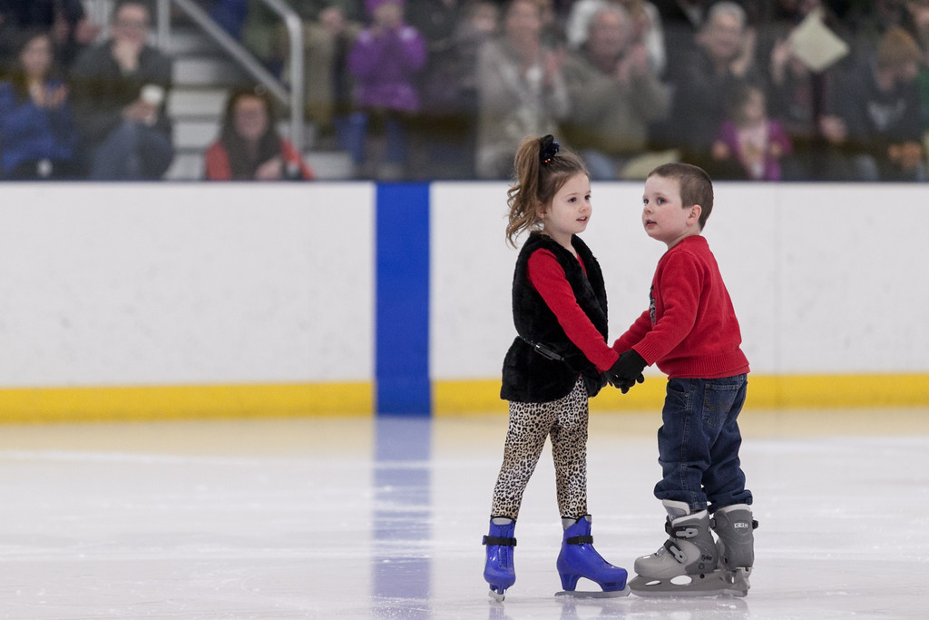 "Tibby McDowell | The Sheridan Press<br /> Ione Crawford, left, and Lucas Tracy clasp hands while performing with their group to ""Moose Mambo"" during the Sheridan Ice's 9th Annual Ice Show at Whitney Rink at  M&M's Center Tuesday, March 27, 2018."