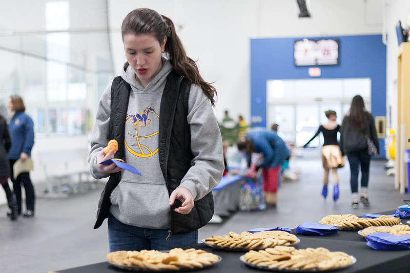 Tibby McDowell | The Sheridan Press<br /> 12-year-old Nora Butler grabs a cookie at the refreshment table during the Sheridan Ice's 9th Annual Ice Show at Whitney Rink at  M&M's Center Tuesday, March 27, 2018.
