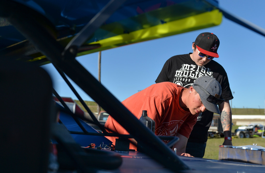 Justin Sheely | The Sheridan Press<br /> B-Mod driver Quinton Rosalez, top, watches as pitman Chandler Case makes some last minute checks in the track pit during the opening race day for the season Friday at Sheridan Speedway. Dirt track racing is has been a long-held favorite summer activity for Sheridan spectators, drivers and organizers. The site reopened in spring of 2015 after being vacant for five years. This month's racing schedule is set on Friday, May 12 and 19, and Thursday, May 25.