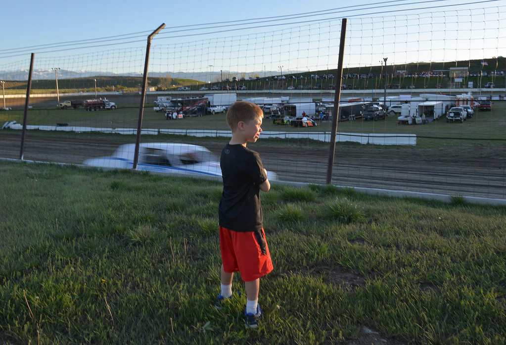 Justin Sheely | The Sheridan Press<br /> Seven-year-old Bryson Adsit watches hobby stock cars compete during the opening race day for the season Friday at Sheridan Speedway. Dirt track racing is has been a long-held favorite summer activity for Sheridan spectators, drivers and organizers. The site reopened in spring of 2015 after being vacant for five years. This month's racing schedule is set on Friday, May 12 and 19, and Thursday, May 25.