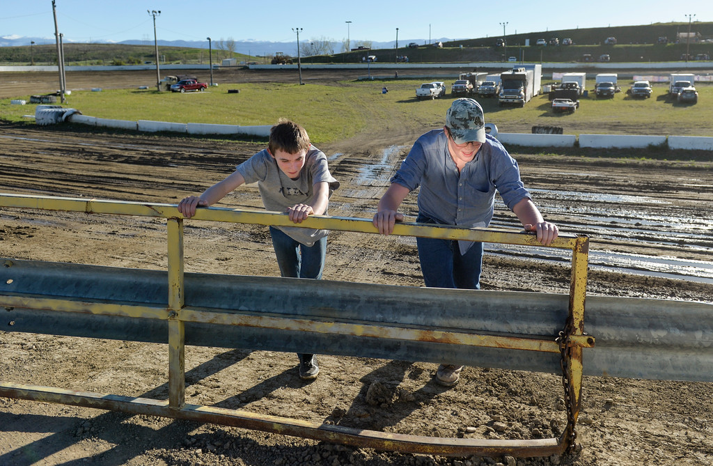 Justin Sheely | The Sheridan Press<br /> Fourteen-year-old Gage Baxter, left, and J.W. Fort, 13, close the gate to the track on the opening race day for the season Friday at Sheridan Speedway. Dirt track racing is has been a long-held favorite summer activity for Sheridan spectators, drivers and organizers. The site reopened in spring of 2015 after being vacant for five years. This month's racing schedule is set on Friday, May 12 and 19, and Thursday, May 25.