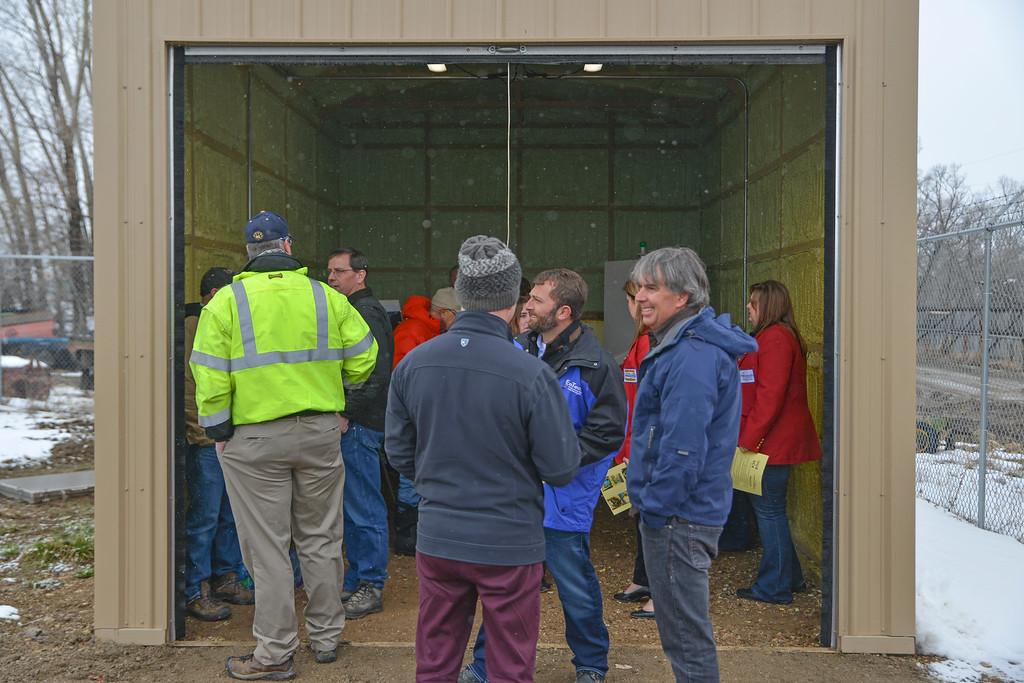 Justin Sheely | The Sheridan Press<br /> City employees, chamber ambassadors and officials take shelter in a garage during the ribbon cutting ceremony at the Beckton Hall hydropower facility Thursday, April 5, 2018. The hydropower station will generate enough electricity to power an estimated 100 homes.
