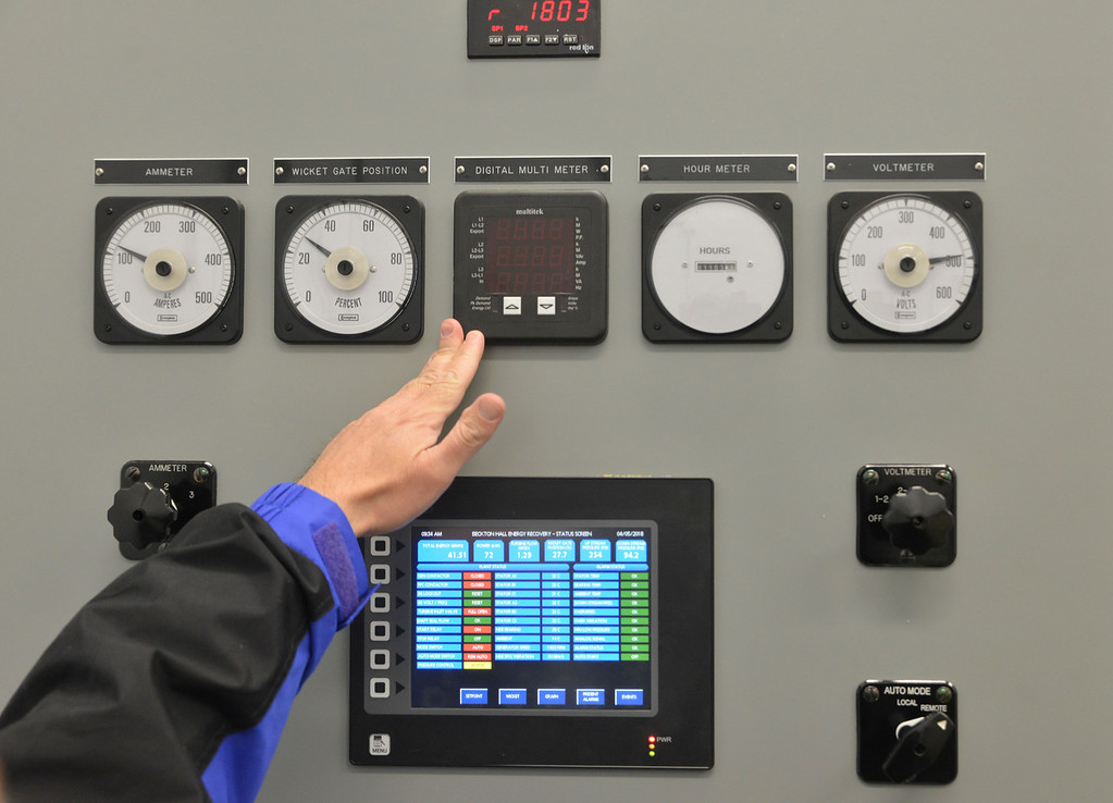 Justin Sheely | The Sheridan Press<br /> Hanns Mercer points to various meters inside the control room during the cutting ceremony at the Beckton Hall hydropower facility Thursday, April 5, 2018. The hydropower station will generate enough electricity to power an estimated 100 homes.