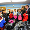 Diego Fagundez of Leominster (second from right), who plays for the New England Revolution professional soccer team, says a few words at the Leominster Spanish American Center as about 1,000 coats are donated to the center as part of Worcester County Sheriff Lew Evangelidis' (right) Annual Winter Coat Drive on Thursday as the center's executive director Neddy Latimer and domestic violence and legal counselor Nicolas Formaggia (both left of Fagundez) and some coat recipients look on.<br /> SENTINEL & ENTERPRISE / BRETT CRAWFORD