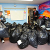 Diego Fagundez of Leominster, who plays for the New England Revolution professional soccer team, helps bring in bags filled with winter coats into the Leominster Spanish American Center for Worcester County Sheriff Lew Evangelidis' (standing at right) Annual Winter Coat Drive. About 1,000 coats were donated to the center on Thursday.<br /> SENTINEL & ENTERPRISE / BRETT CRAWFORD