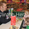 Clinton police officer Ben Huizenga, Victoria Sanborn, 7, and Zoey Olsen, 6, of Clinton talk about the exciting presents they purchased during the Shop with a Cop event on Saturday at Target. • Katie Dahlstrom/Clinton Herald