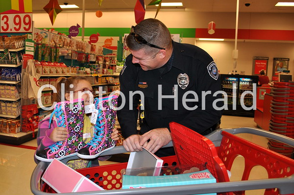 Amelia Gomez, 7, of Clinton shows Clinton police officer Dean Ottens the boots she wanted to get during the Shop with a Cop event on Saturday at Target in Clinton. • Katie Dahlstrom/Clinton Herald