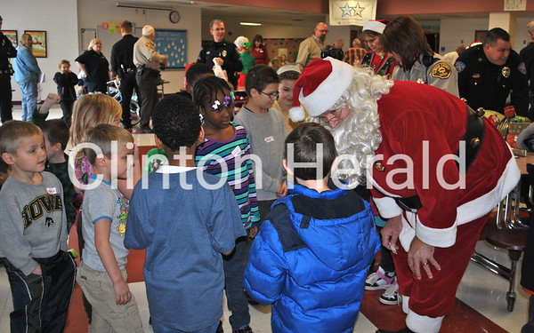 Santa Claus talks to the children who were part of the annual Shop with a Cop event on Saturday at Bluff Elementary. • Katie Dahlstrom/Clinton Herald