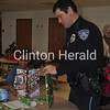 Tyreke Foster, 8, of Clinton, beams at his new toys while officer Dan Sager wraps the other presents they purchased together during the Shop with a Cop event on Saturday at Bluff Elementary School. • Katie Dahlstrom/Clinton Herald