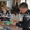 Grace Crowe, 7, of Clinton, wraps presents with Camanche police officer Damien Houzenga during the Shop with a Cop event on Saturday at Bluff Elementary School. • Katie Dahlstrom/Clinton Herald