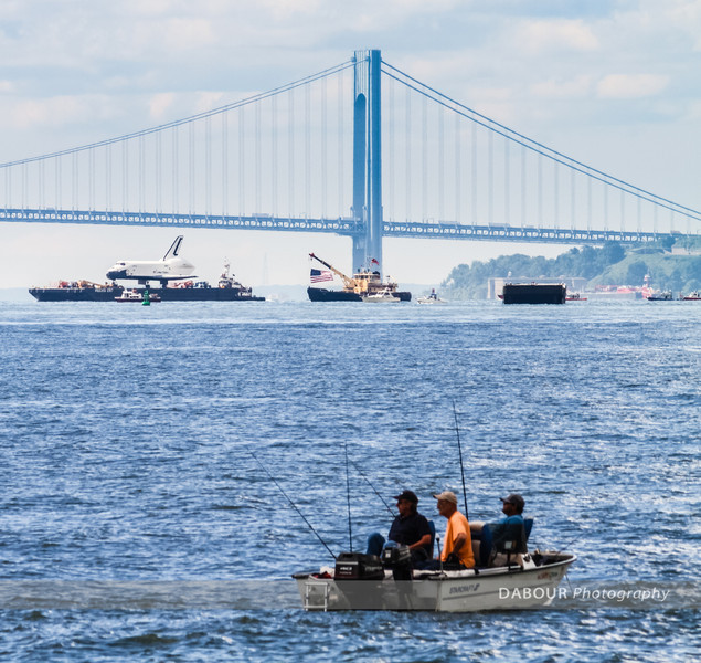 Fishermen almost appear more interested in fishing than the space Shuttle Enterprise passing by near Liberty State Park. Express-Times photo by | DAVE DABOUR