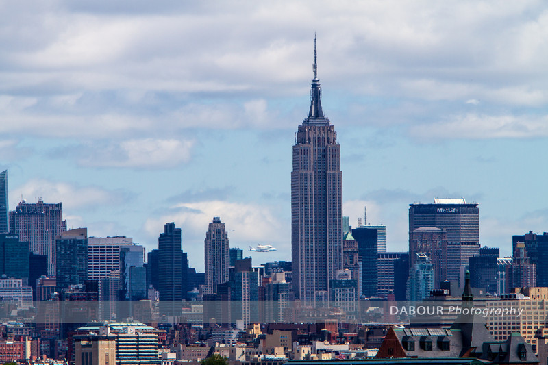 The Space Shuttle makes a fly-by in the NYC area passing behind the Empire State Building.