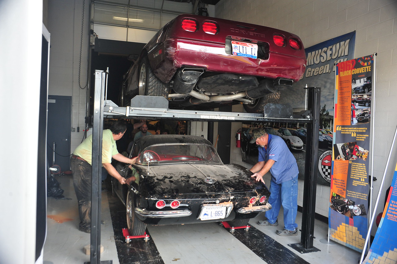 """The 1993 40th Anniversary """"Ruby"""" Corvette and the 1962 Black Corvette are placed in a temporary display location while construction is underway in the Skydome. Ironically, they are displayed much like they were pre-sinkhole in the Skydome, on and under a lift."""