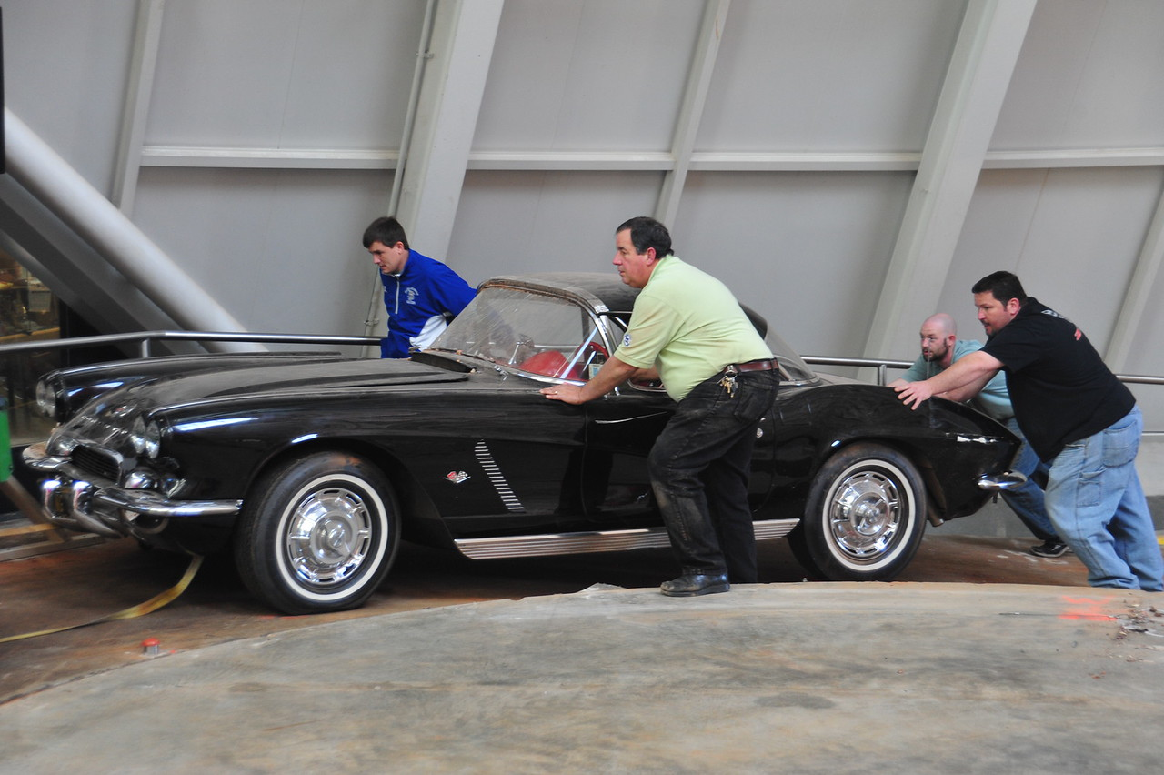 Museum facilities team members help push the 1962 Tuxedo Black Corvette out of the Skydome.  The next time the car enters the space for display, it will be restored to its former glory.