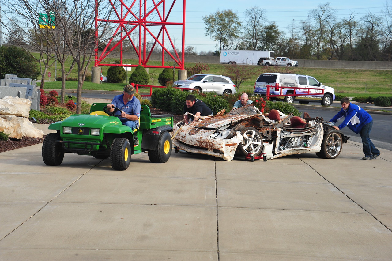"With the help of a John Deere Gator, Museum team members move the 2009 ""1.5 Millionth"" Corvette from the Skydome to a new display spot in the lobby of the Museum. The car suffered major damage and will not be repaired."