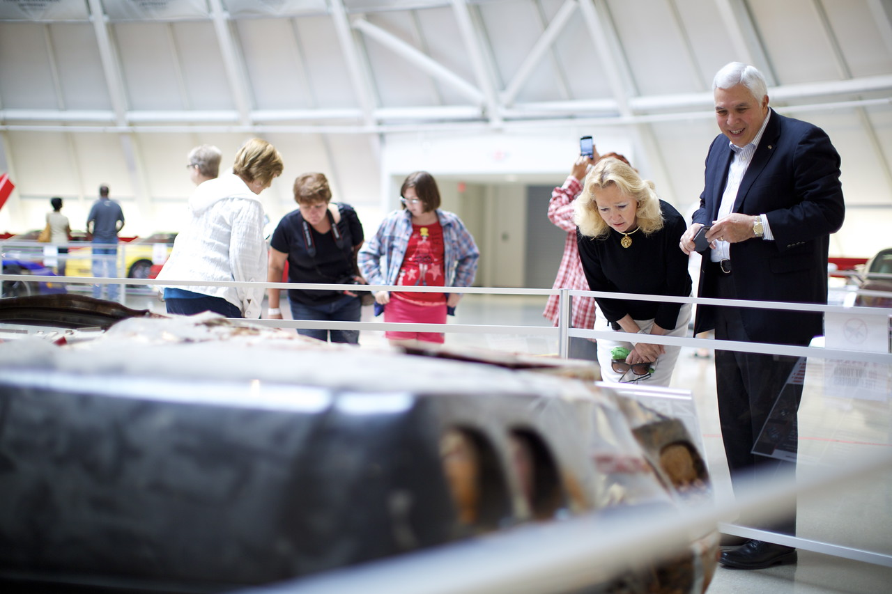 "Visitors read the story behind the damaged ""sinkhole Corvettes."" Photo by Maddie Powers / National Corvette Museum"