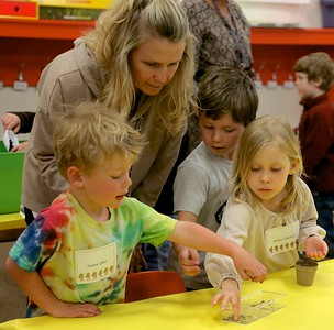 As teacher Karen stoneback watches, this fall's kindergarden students pick out sunflower seeds for planting so they will know school starts for them when there sunflower blooms ,