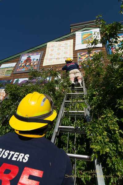 Sisters Fire Department crews hang quilts from the Employee Challenge on the 2 story wall of Jean Wells' Stitchin' Post at the Sisters Outdoor Quilt Show - July 14, 2012 - Sisters, Oregon - Gary N. Miller - Sisters Country Photography