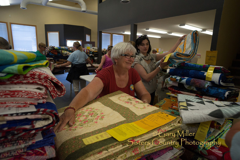 At 4:30 when the 1400 quilts are taken down and crowds go home work shifts are just starting for crews in the intake and distrubution center as they all have to be inspectied, folded, sorted, scanned and readied for either shipment or pickup back to their owners on Monday. 2013 Sisters Outdoor Quilt Show - The largest outdoor quilt show in the world with over 1,400 quilts on display was held in Sisters, Oregon on July 13, 2013 - Copyright © 2013 Gary N. Miller, Sisters Country Photography