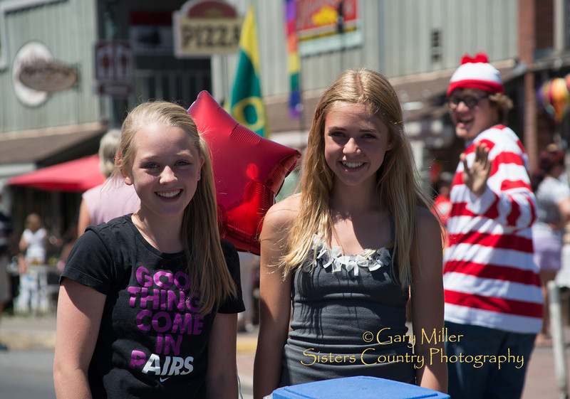 Water girls smile as Waldo whizzes by at the 2013 Sisters Outdoor Quilt Show - The largest outdoor quilt show in the world with over 1,300 quilts on display was held in Sisters, Oregon on July 13, 2013 - Copyright © 2013 Gary N. Miller, Sisters Country Photography