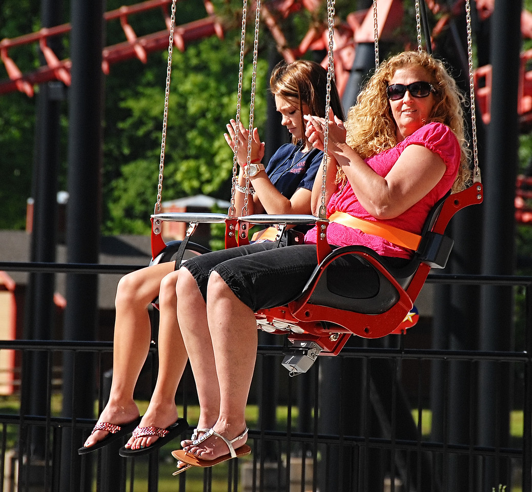 05-09-13  --skyscreamer 04--  WellStar Health System employee Rhonda Holcombe, right, and her daughter Tiffany Bass applaud as they are lowered to the ground after riding the new SkyScreamer ride at Six Flags Over Georgia on Thursday morning.  STAFF/LAURA MOON.