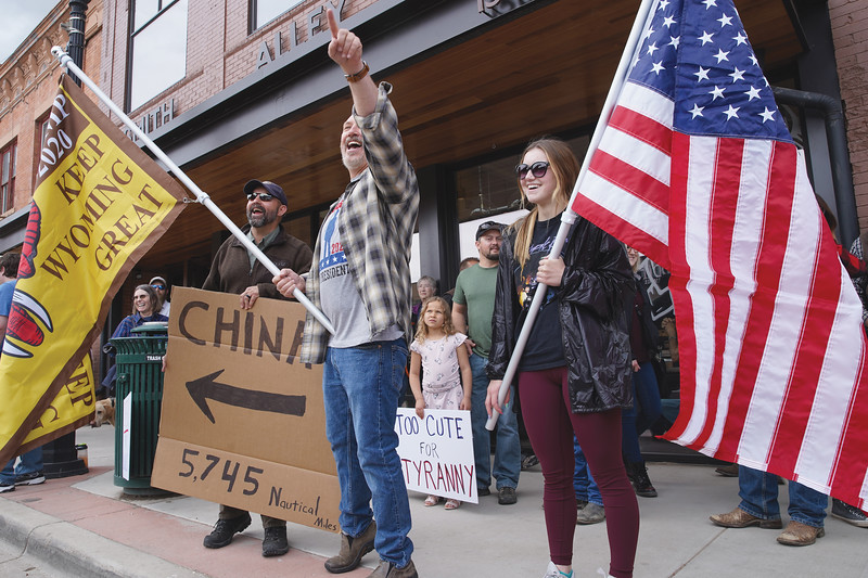 Matthew Gaston   The Sheridan Press<br>Protestors, from left, Brad Walden, Kent Sherwood and Camdyn Cook smile and wave to passersby on Main Street during the freedom rally at Smith Alley Brewing Company Friday, May 16, 2020.