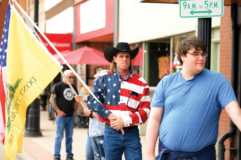 """Matthew Gaston   The Sheridan Press<br>John Syzmaniak holds a """"Don't Tread on Me"""" flag during the freedom rally at Smith Alley Brewing Company Friday, May 15, 2020."""
