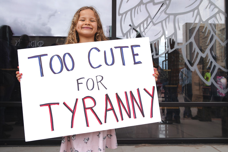 """Matthew Gaston   The Sheridan Press<br>Six-year-old Scarlett Cureton holds a sign reading, """"TOO CUTE FOR TYRANNY,"""" during the freedom rally at Smith Alley Brewing Company Friday, May 16, 2020."""