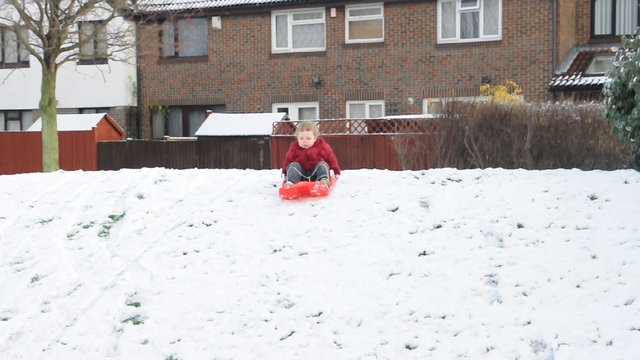 Sledging down the small hill near our house