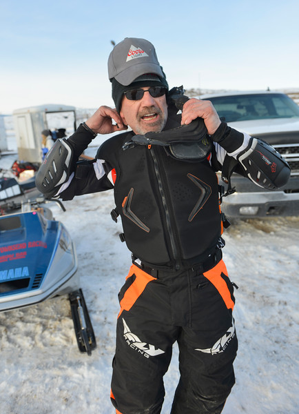 Justin Sheely | The Sheridan Press<br /> Driver Tom Kostreba puts on a neck brace at the staging area during the snowmobile racing event at Sheridan Speedway Saturday, Jan. 27, 2018. This was the first time Sheridan hosted the Extreme Mountain Racing circuit.