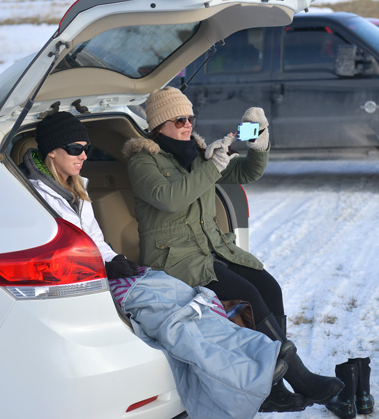 Justin Sheely | The Sheridan Press<br /> Cassie Gammel, left, and Caroline Houck watch from the back of their car during the snowmobile racing event at Sheridan Speedway Saturday, Jan. 27, 2018. This was the first time Sheridan hosted the Extreme Mountain Racing circuit.