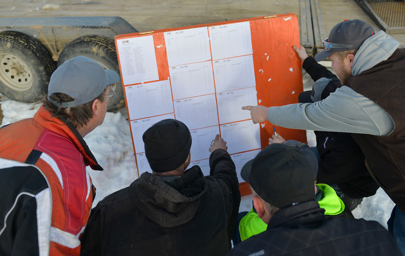 Justin Sheely | The Sheridan Press<br /> Drivers look over the event sheets during the snowmobile racing event at Sheridan Speedway Saturday, Jan. 27, 2018. This was the first time Sheridan hosted the Extreme Mountain Racing circuit.