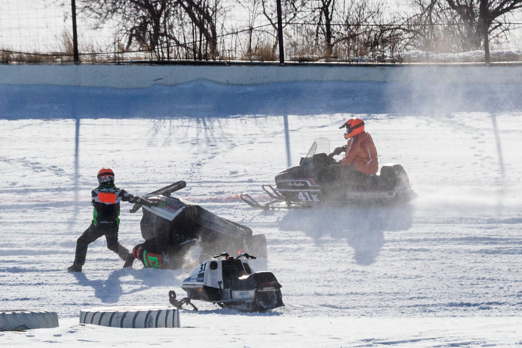 Tibby McDowell | The Sheridan Press<br /> <br /> Dave Leniger, left, and Dave Stromberg, center (under sled), collide and flip in the Fan Cooled Stock (Vintage) heat of the X-Treme Mountain Racing snommobile races at Sheridan Speedway Saturday Jan. 27, 2018.